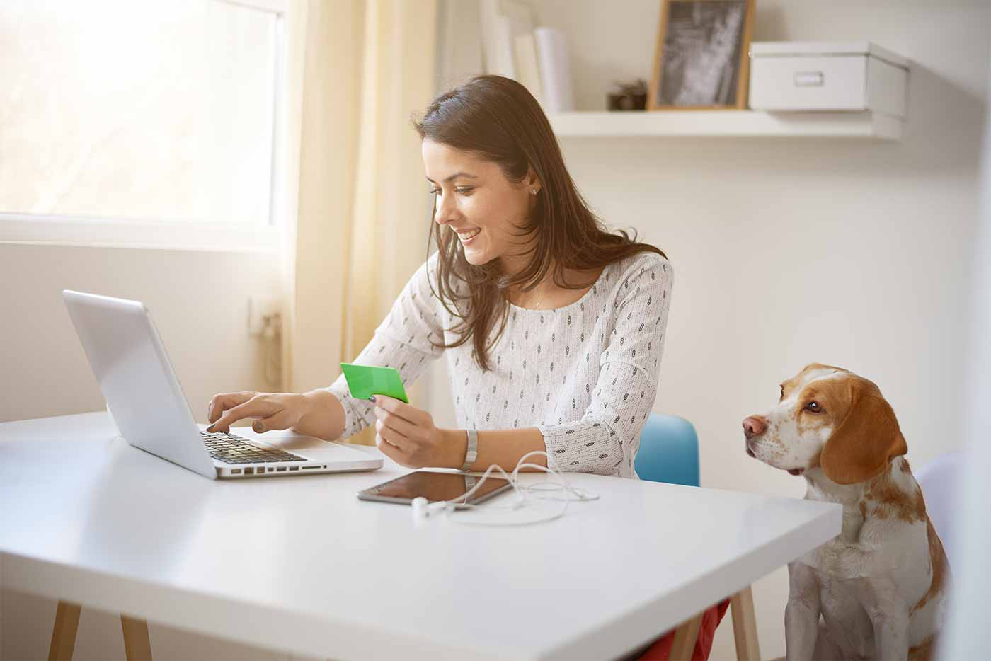 Homeowner and dog happily applying for financing online.